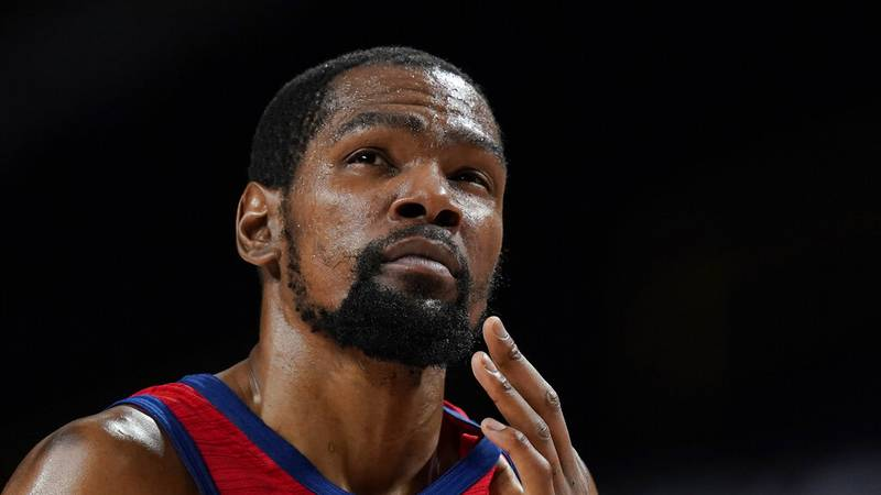 United States's Kevin Durant reacts after he collided with another player and hit his face...