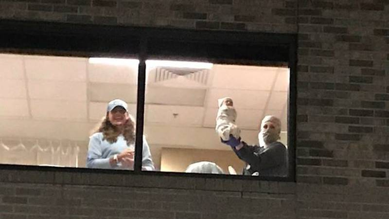 New father Tommy Edwards shows off his baby to family waiting in the parking lot below at...