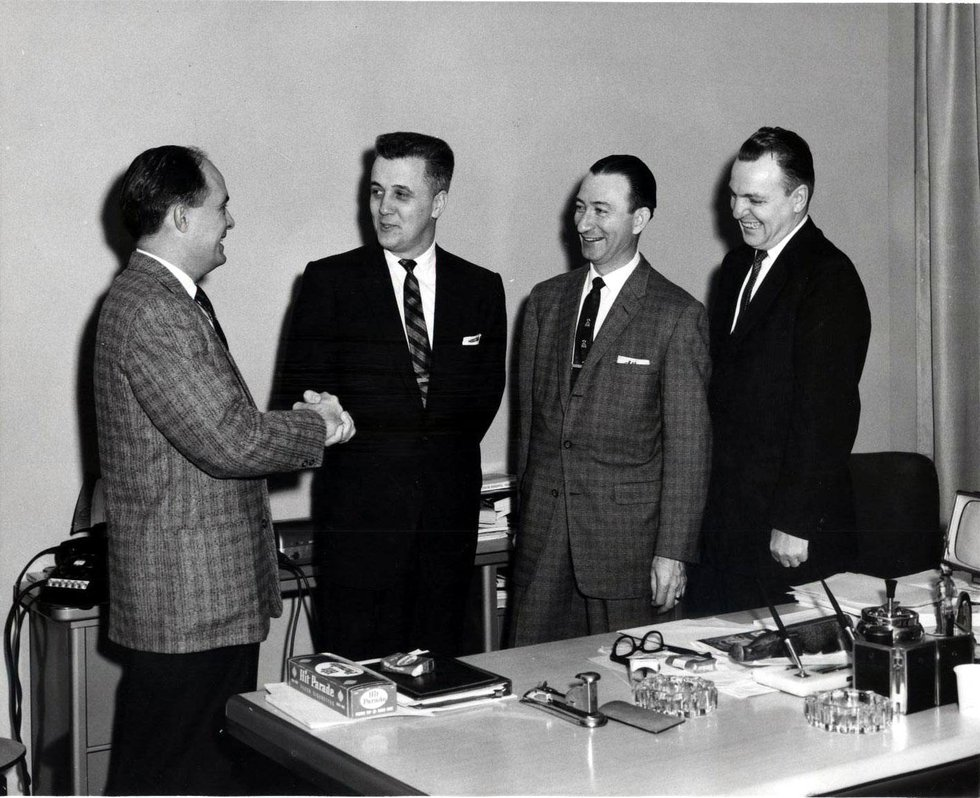 A handshake seals the deal for the sale of WSFA radio. It only remained at the Delano Avenue...