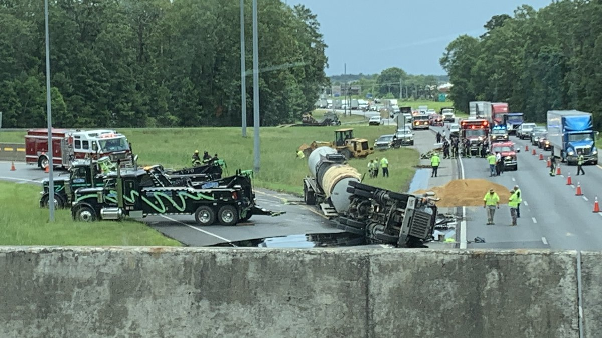 Two large two trucks work to remove an 18-wheeler that was carrying asphalt when it overturned...