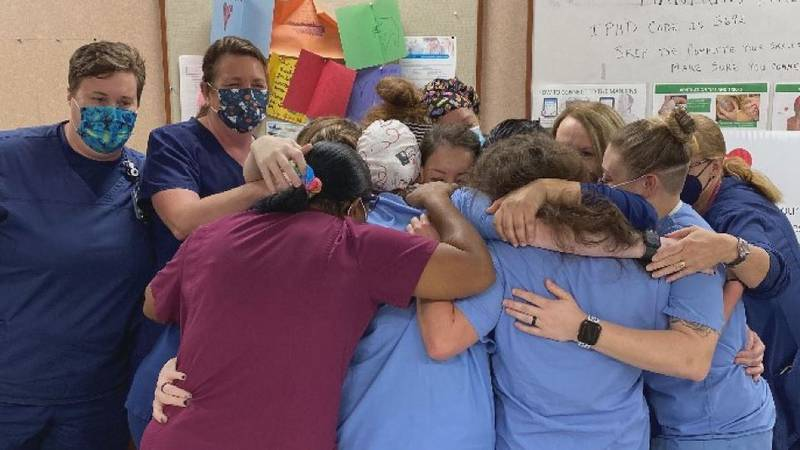 Emergency staff at Memorial Hospital have a group hug celebration for one of its own after...