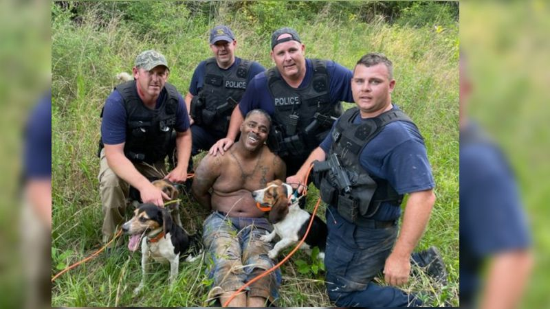 Police pose with the man they say robbed a Prentiss bank following the manhunt to capture him.
