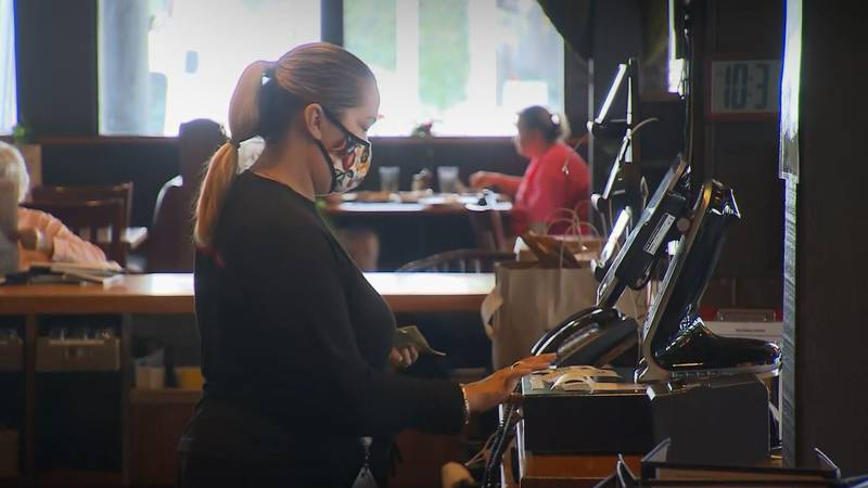 A restaurant staffer wears a face mask while working.