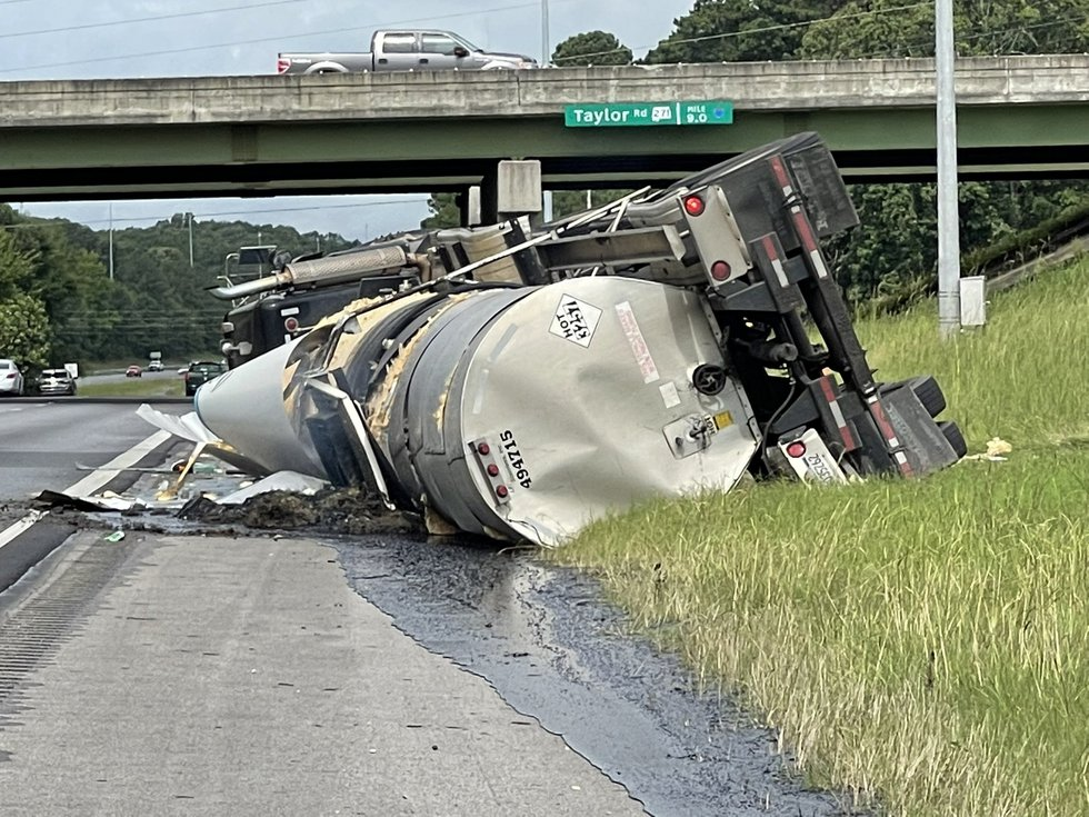 An 18-wheeler hauling a load of asphalt overturned from the Taylor Road on-ramp to the...