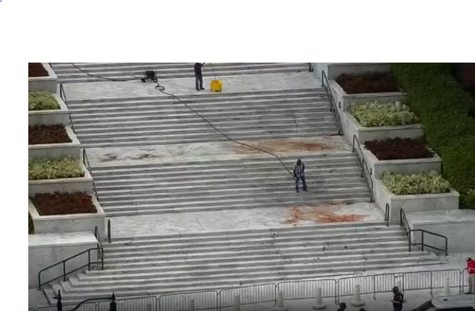 Crews work to clean an unknown red substances off the steps of the Alabama Capitol Wednesday...