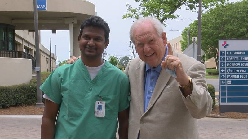 Dr. Vamshi Balasetti poses for a photo with patient Michael Amos. Balasetti's thrombectomy...