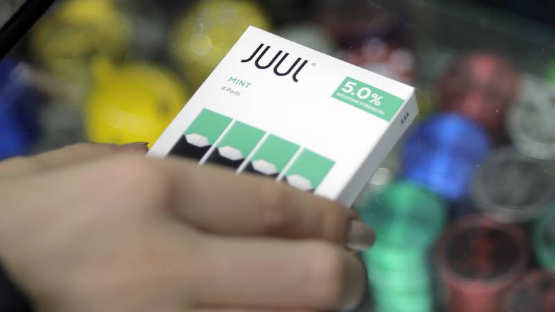 A woman buys refills for her Juul at a smoke shop in New York, Thursday, Dec. 20, 2018. Altria,...