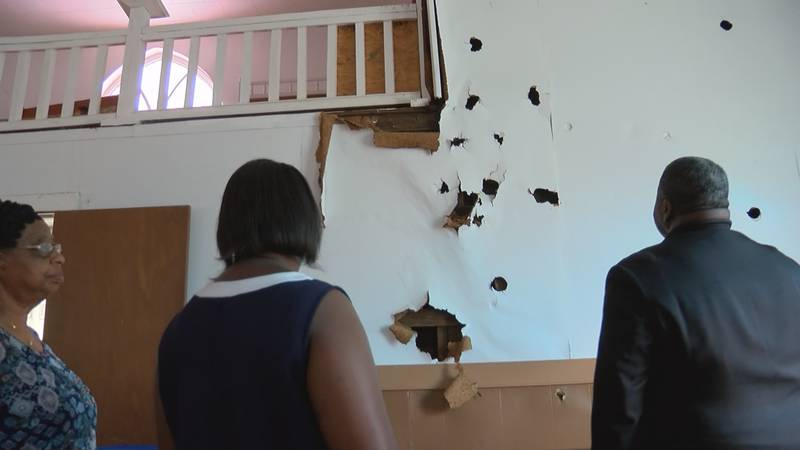 Church members assess the damage done to their church following the break-in.