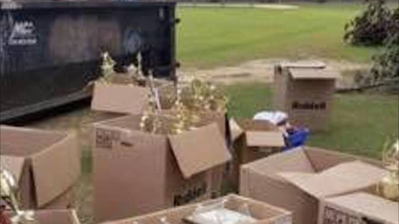 High school trophies marking athletic milestones are boxed and placed next to dumpster.  Photo...