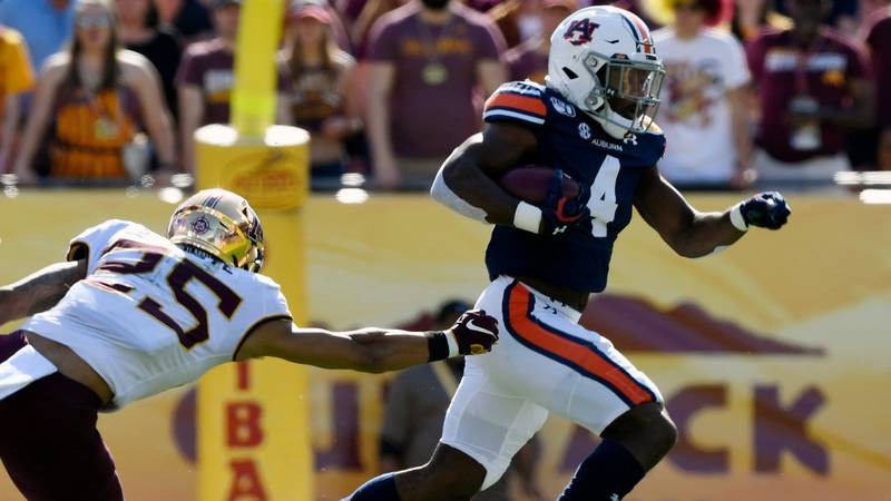Noah Igbinoghene (4) returns a kickoff for a TD in the first half.Auburn football Outback Bowl...